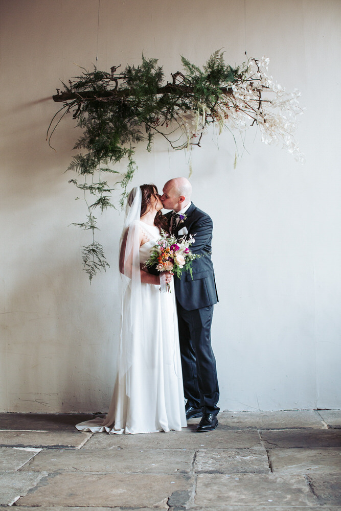 Bride and groom portrait at The Arches, kissing under a beautiful fern archway.