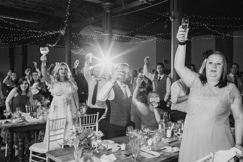 Wedding guests raise their glasses for a toast.