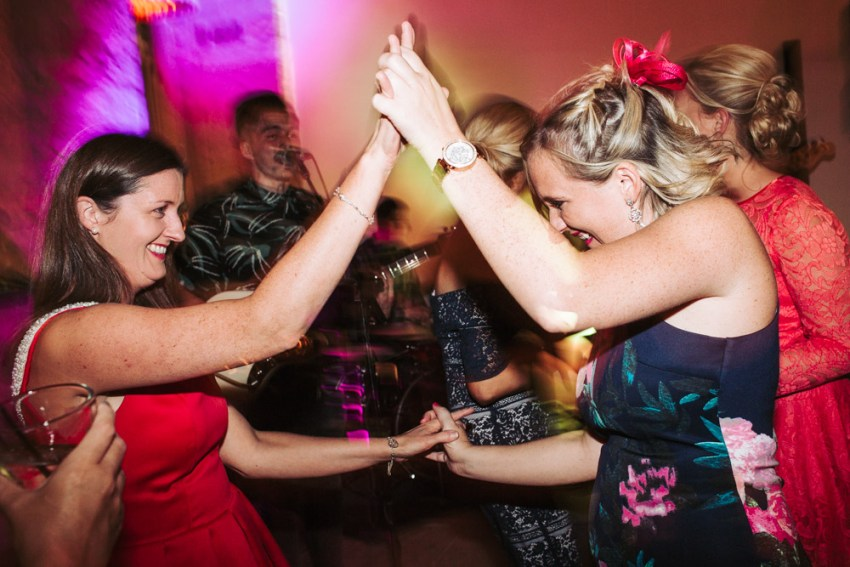 Two ladies dancing together at a wedding.