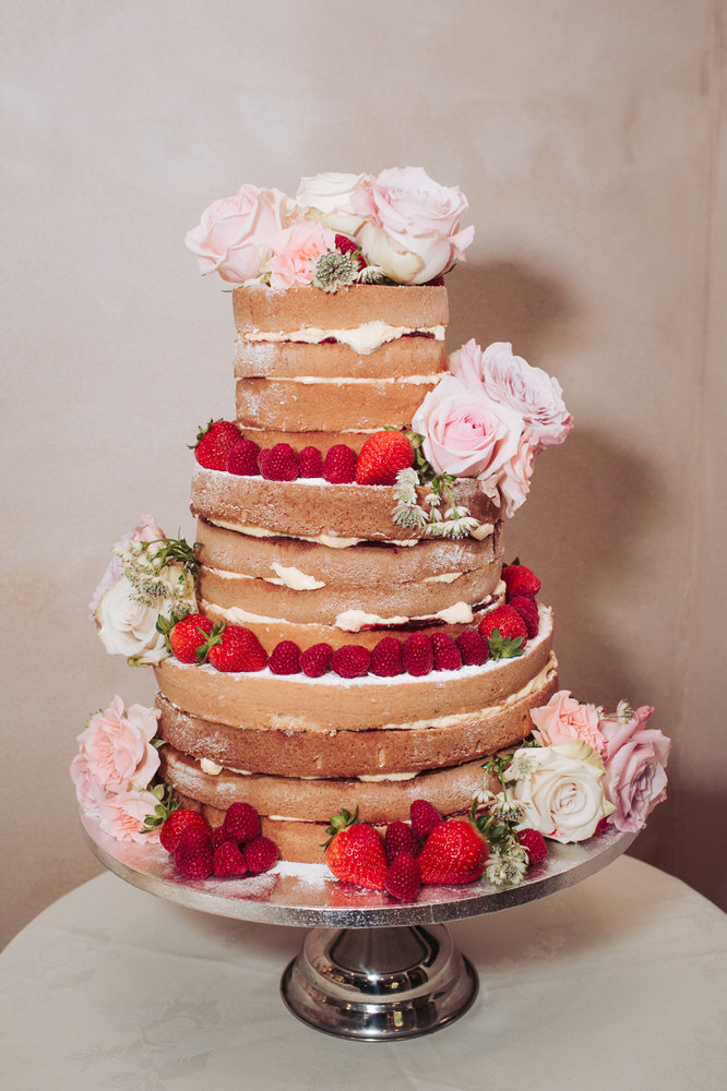 Wedding cake naked cake decorated with roses and fruit.