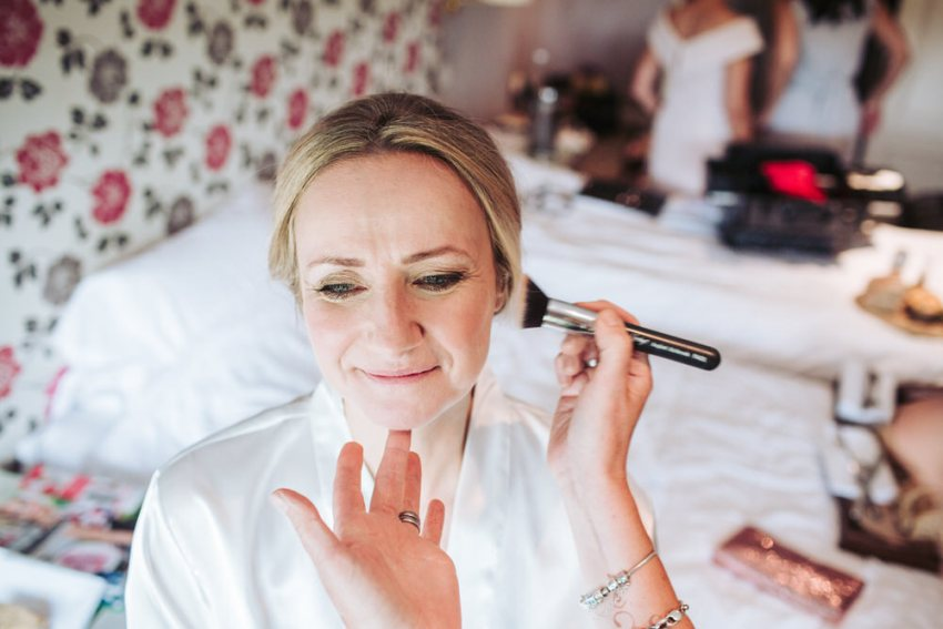 Makeup artist applies blushes to bride.