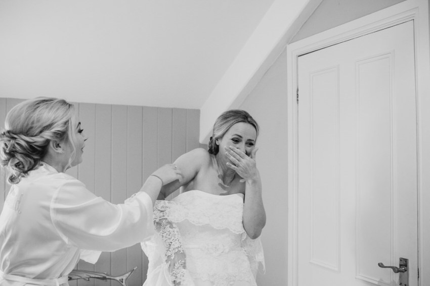 Bride hold back tears as her daughter helps her into wedding dress at the Devonshire Fell in Burnsall.