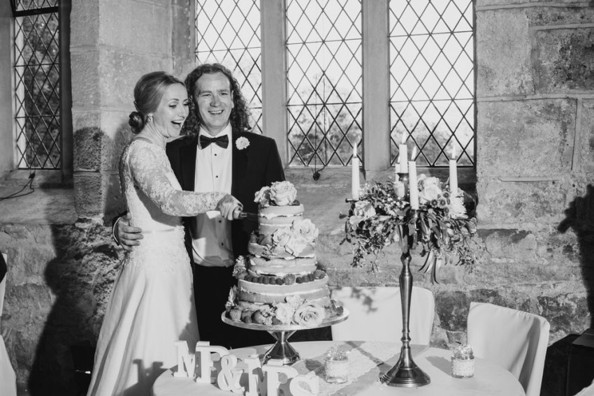 Bride and groom cut the cake at Bolton Abbey Barden Tower.