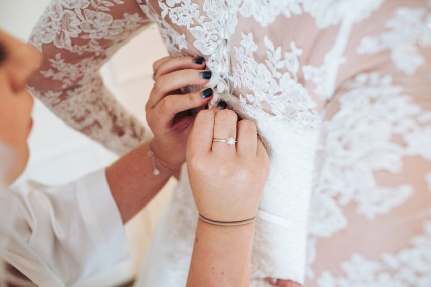 Brides daughter fastens the back of her lace wedding dress.