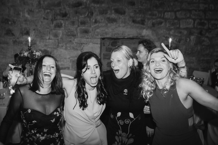Group of ladies with arms around each other while singing on wedding dance floor.