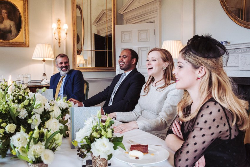 People laughing at wedding breakfast table.