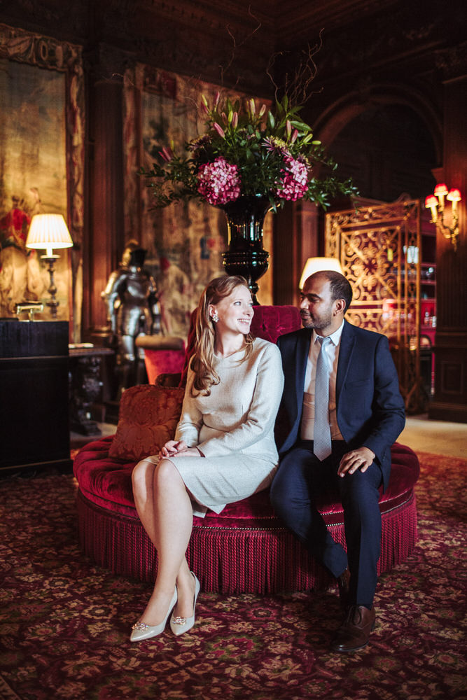 Cliveden House wedding photographer. Bride and groom sit together in the hotel foyer.