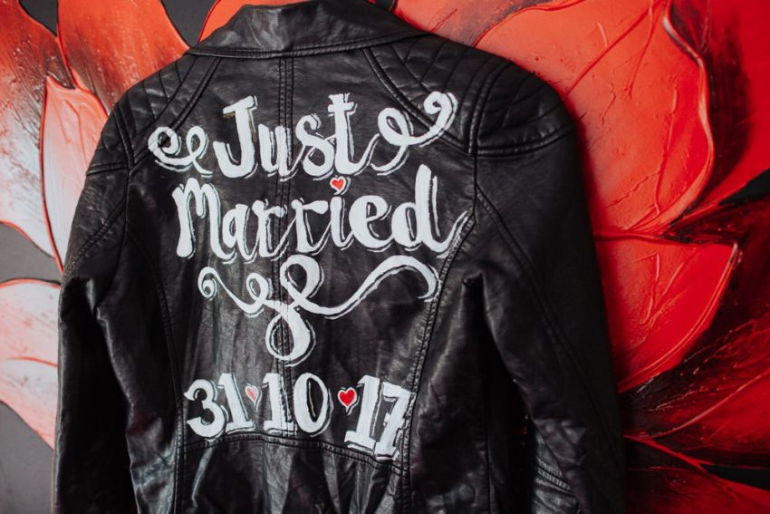 Cool brides black leather jacket with painted hand lettering saying 'Just Married'.