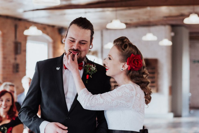 Rockabilly bride wipes lipstick off grooms face after the first kiss.