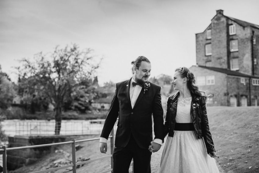 Rockabilly bride and groom walk by the river at West Mill.