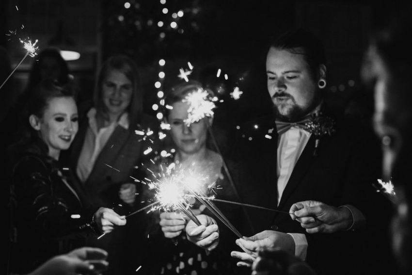 Groom lights sparklers with guests.