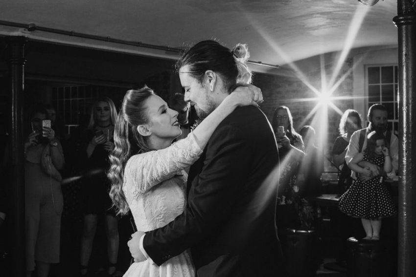 Bride and groom hold each other for their first dance.