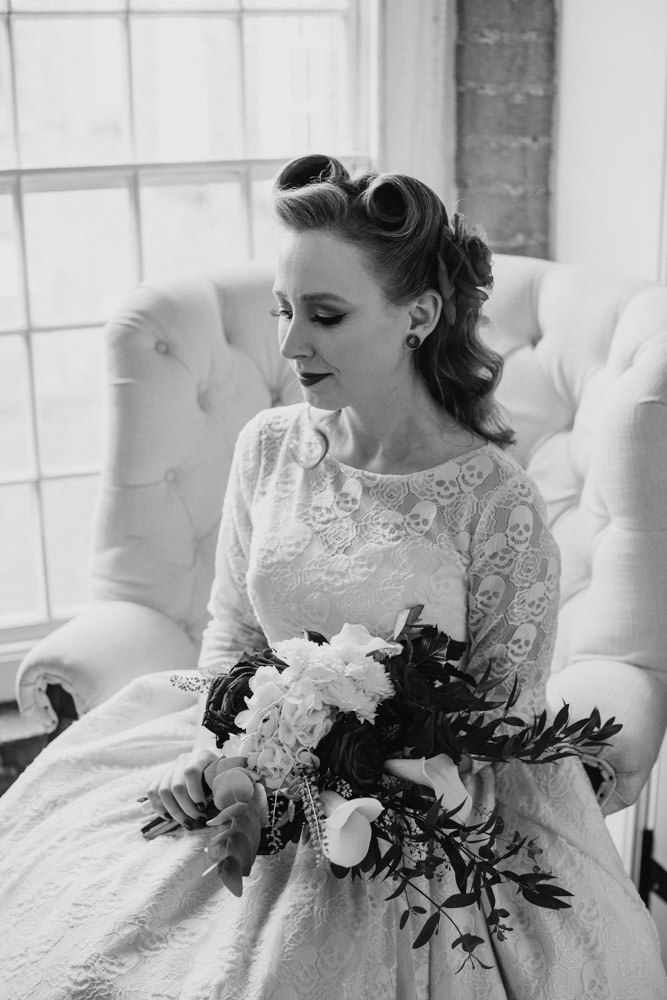 Portrait of rockabilly bride wearing lace skull dress for Halloween wedding.