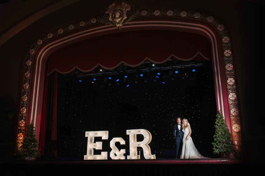 Kings Hall & Winter Gardens wedding photographer, Ilkley, Leeds | Bride and groom on theatre stage.