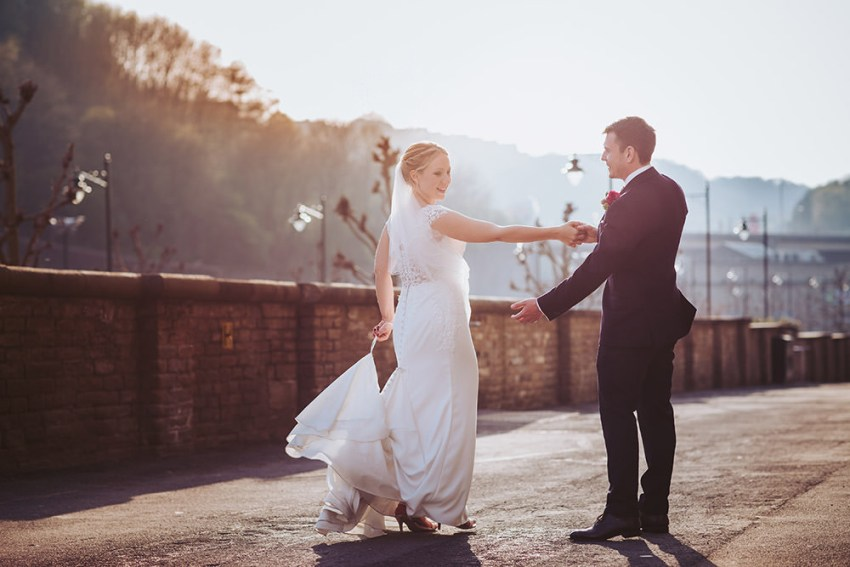 Bride and groom dance outside at the Arches in Halifax. Natural wedding photography UK.