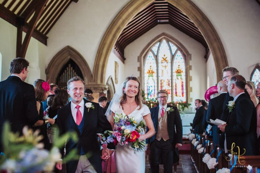 Bride and groom walk down isle at All Saints church in Staveley.