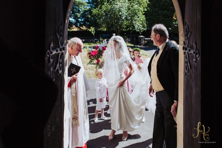 Bride greeted outside All Saints Church doorway in Staveley by the vicar.