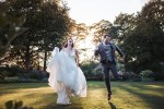 East Riddlesden Hall weddings. Newly wed couple skip across the lawn, bride wears Essense of Australia dress.