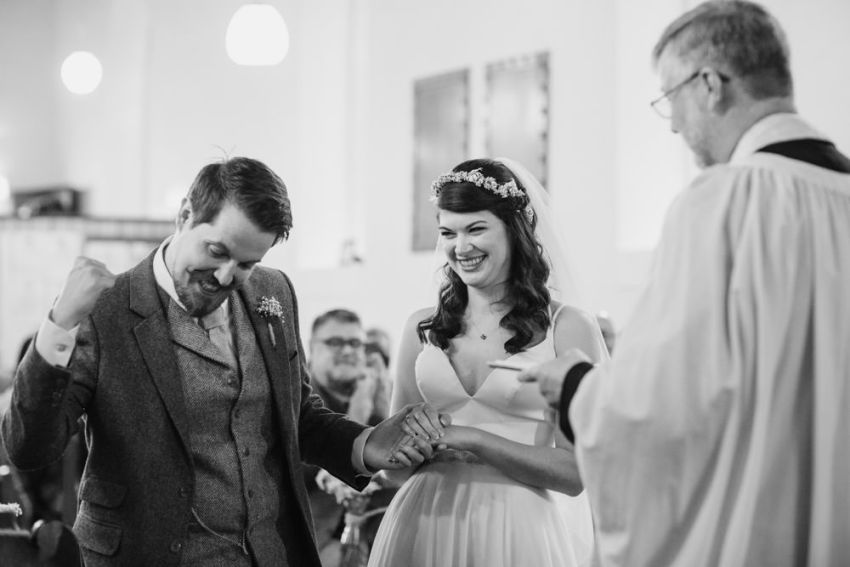 Groom punches air in happiness while vicar announces the couple man husband and wife.