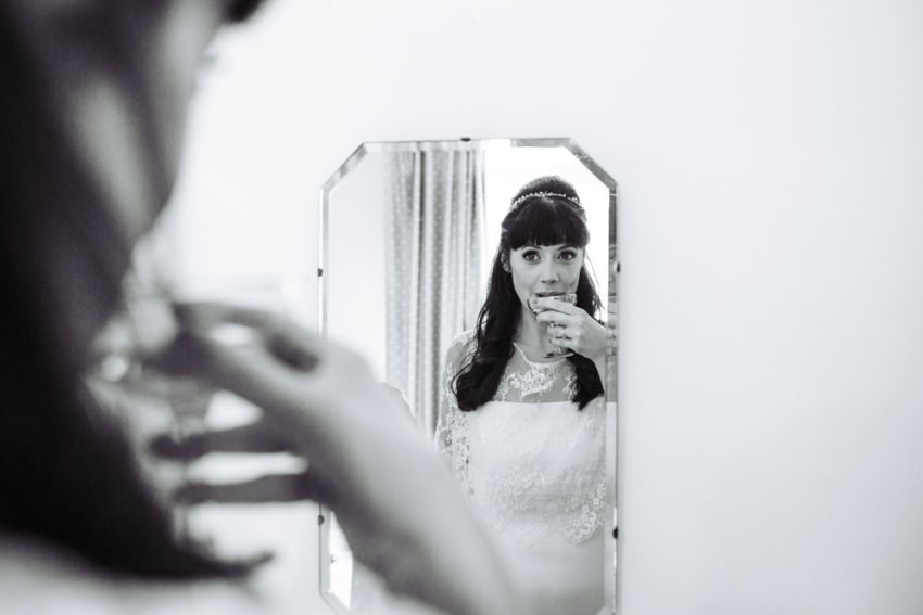 Bride drinks champagne, reflected in mirror.