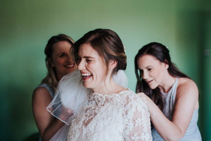 Bridesmaids help bride into her dress.