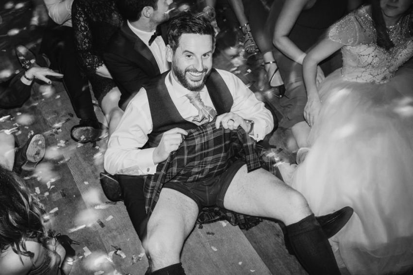 Groom sat on dance floor showing off his boxer shorts under his kilt.