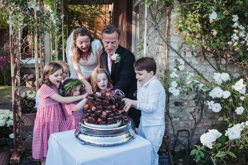 Harrogate wedding. Bride and groom cut the chocolate brownie wedding cake with the help of children.