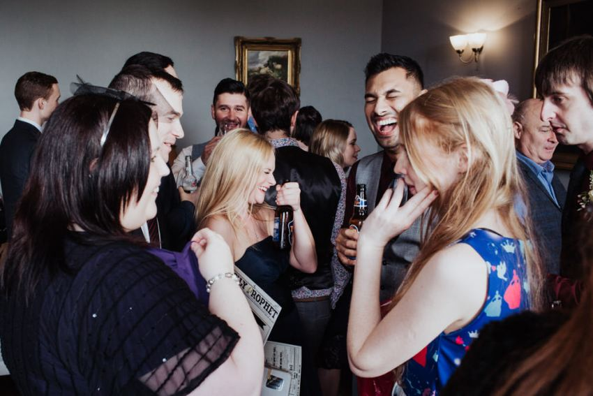 Fun documentary wedding photography of wedding guests laughing.