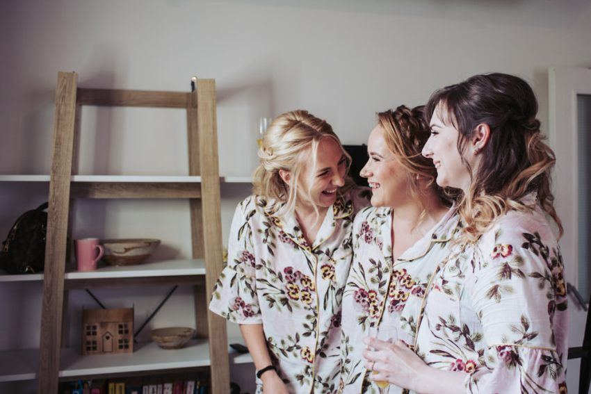 Bridesmaids in matching pyjamas laughing.
