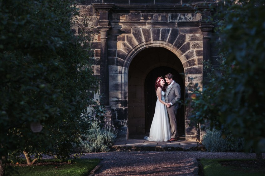 Natural East Riddlesdan Hall wedding photography. Couple stand in the hall doorway.