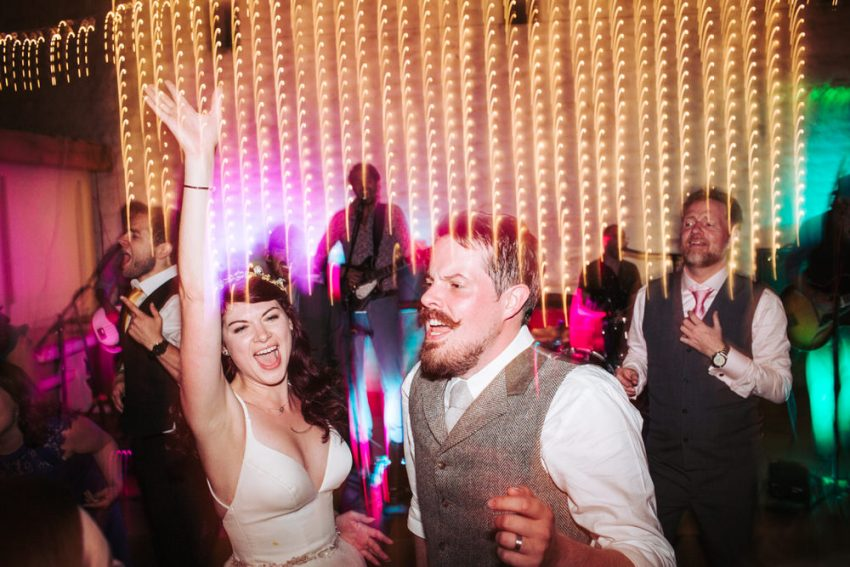Bride and groom on dance floor in Airedale barn.