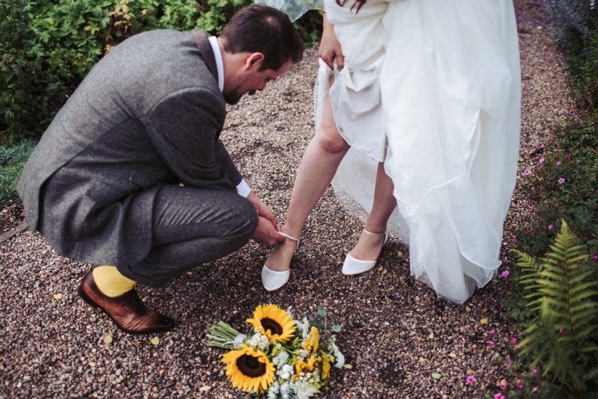 Groom fastens brides shoe, his yellow socks peeping and sunflower bouquet on the ground.