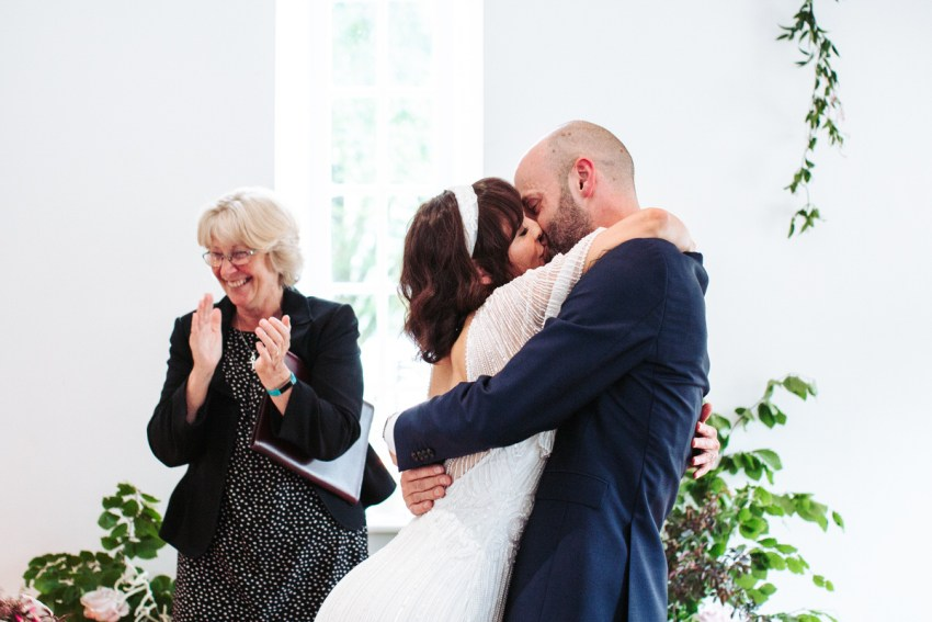The bride launches herself on the groom for the first kiss.