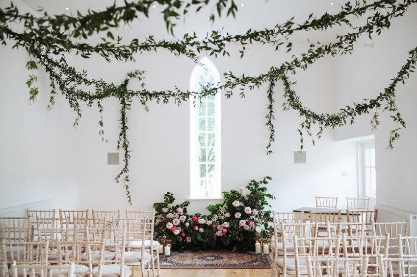 The Coach House, the ceremony room for a Silverholme Manor wedding, decorated with foliage garlands and floral displays.