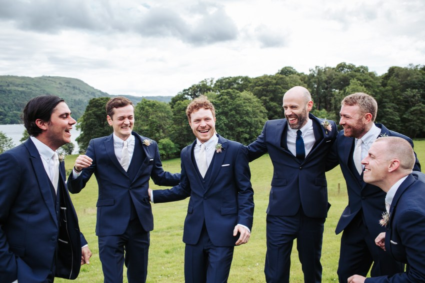 The groomsmen laugh together on the lawn at a Silverholme Manor wedding in the Lakes.