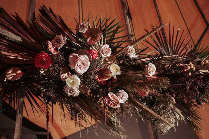 Large floral hanging in a tipi. With pink and white roses and peace lilies and palm leaves sprayed gold.