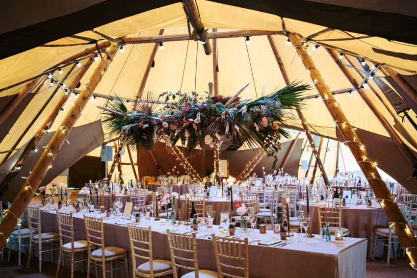 The tipi is set up for the wedding reception with large floral hanging over the top table at a Silverholme Manor wedding.