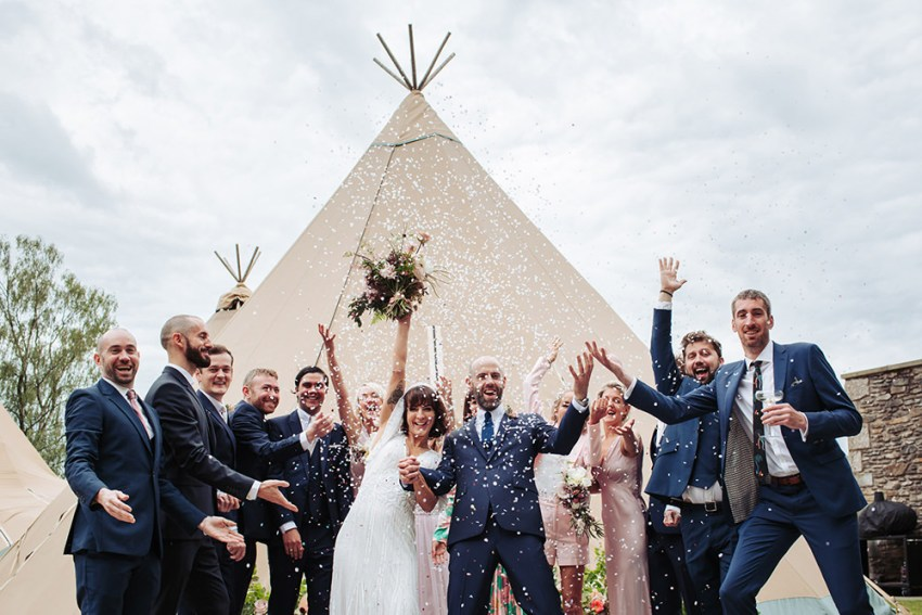 Silverholme Manor wedding photography. Guest throw confetti over the bride and groom in front of a tipi in the Lake District.