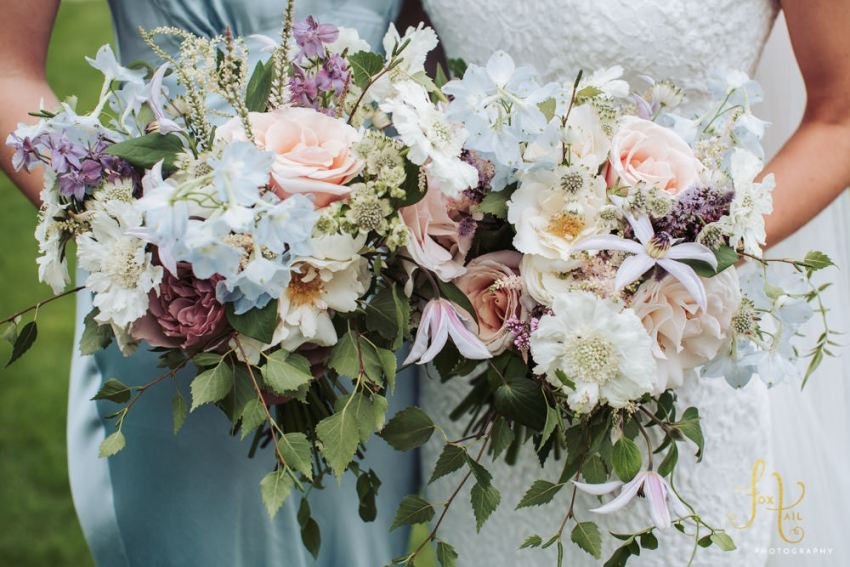 Close up of wedding bouquets by Lucy MacNicill Floral Design. Bouquets contain pale blue delphiniums, large white scabious, peach roses, and clematis flowers.