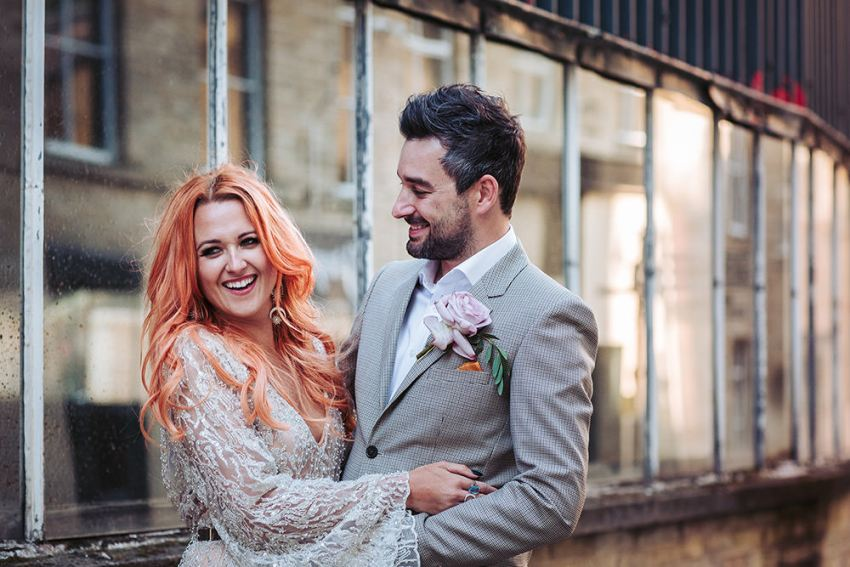 Bride with orange hair in arms of groom in pale grey suit at Arches wedding venue.