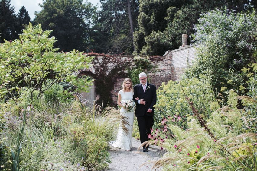 Father of the bride walks the bride through the walled gardens at Fig house wedding, Middleton Lodge.