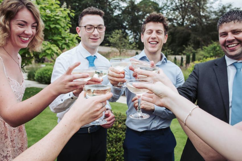 A group of wedding guests clink glasses of champagne together.