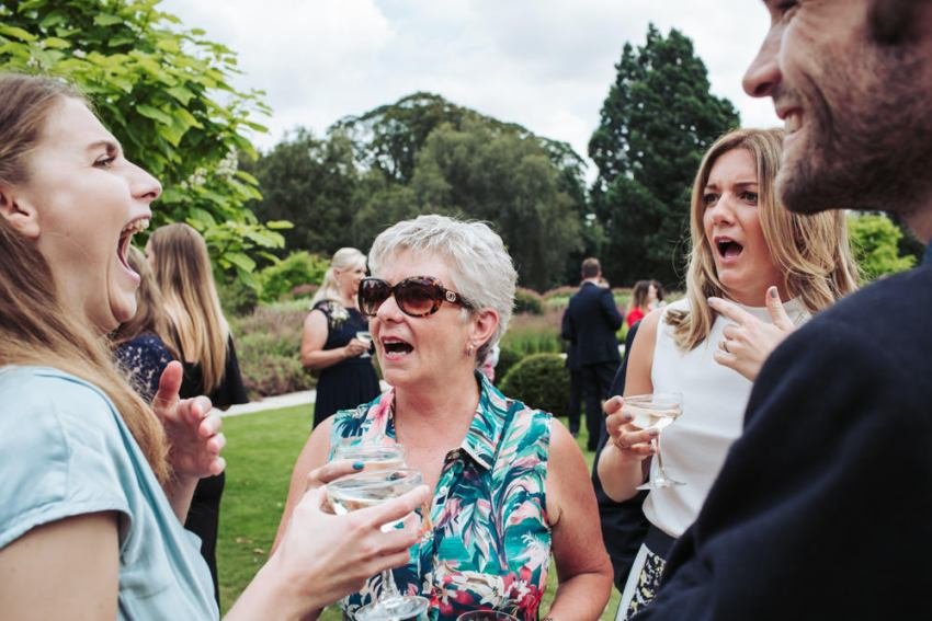 Natural candid moment capturing laughing and shocked faces of wedding guests.