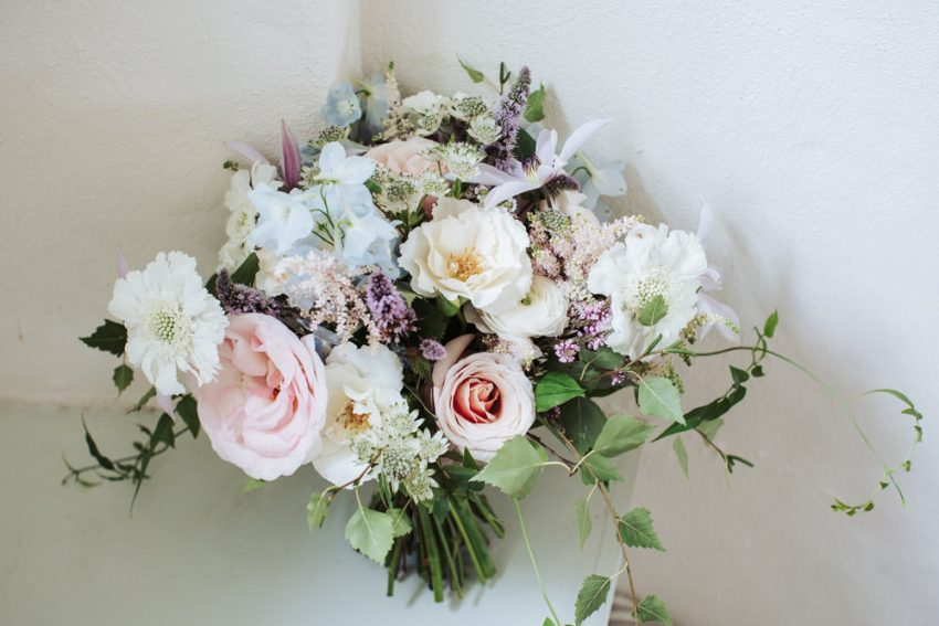 Romantic pastel coloured wedding bouquet with white, pink, blue and purple florals.