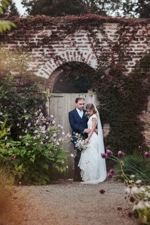 The Fig House walled garden, wedding photography. Bride and groom hold each other by a garden gate. Middleton Lodge