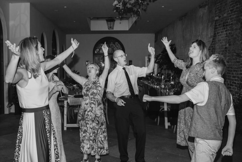 A group of guests sing and dance with their arms thrown in the air.