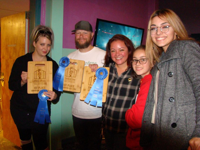 Two women, two children and one man posing with 1st place awards