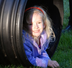 girl climbing in tube at fall festival