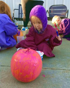 young girl painting a pumpkin