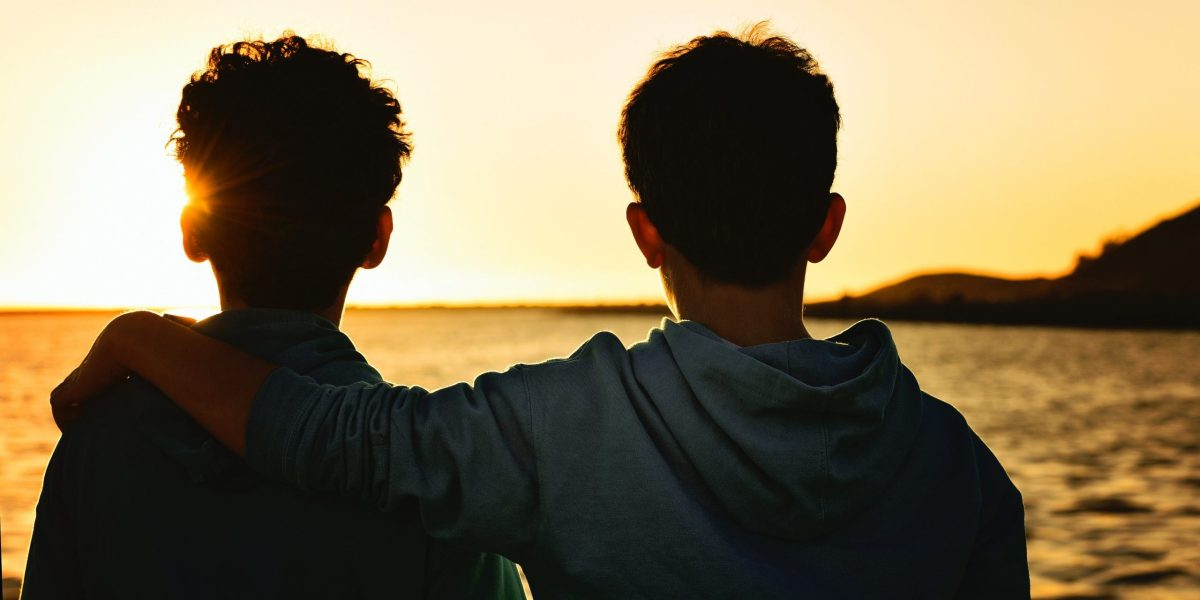 close-up photography of two men facing on seashore during sunset